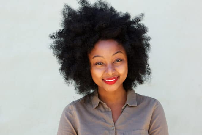 Black woman with curly hair wearing red lipstick and gray collared dress shirt.