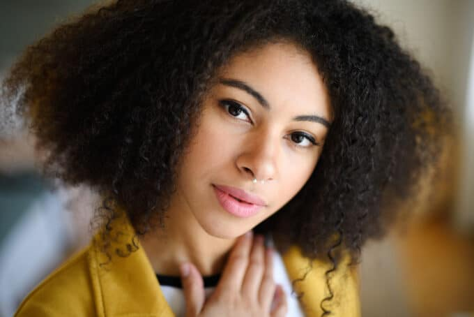 African American women with 4a curls wearing a white t-shirt and a yellow jacket