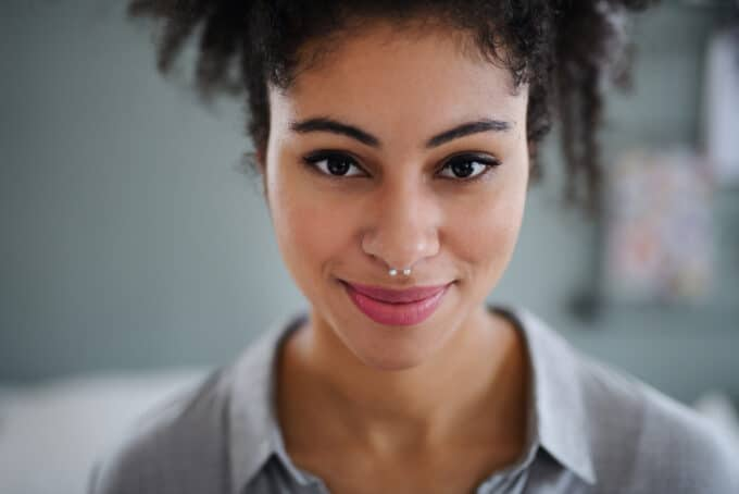 Black women wearing a nose ring, pink lipstick, and pineapple hairstyle