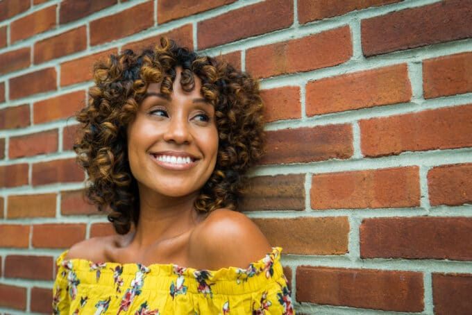 Beautiful African American female with Shirley Temple curls leaning against a brick wall