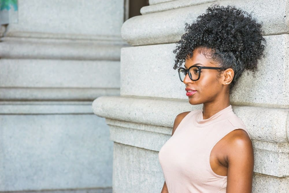 African American women with 4A natural hair thinking about the origin of black seed oil while leaning on a stone wall.