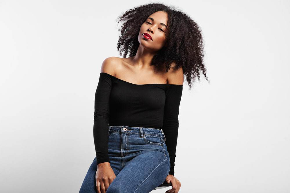 Black adult women sitting on a start wearing blue jeans, and a black shirt, with wavy type 4a natural hair.