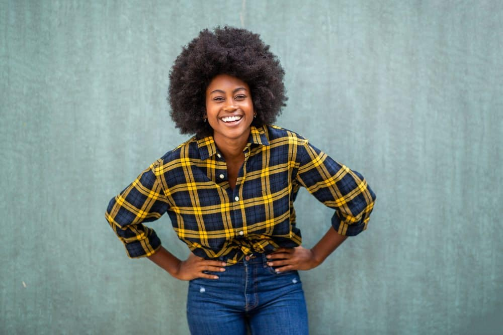 Black female with her hands on her hip wearing a plaid shirt.