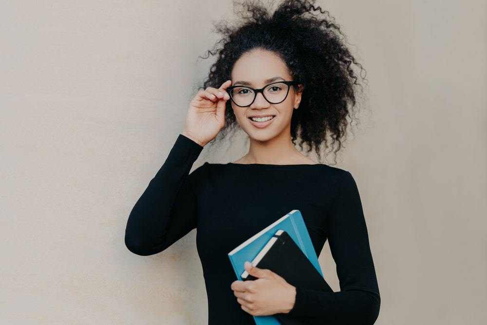 Cute black female with frizzy hair wearing a black sweater, reading glasses and carrying two hair care journals.