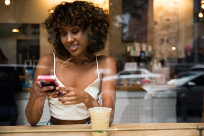 Black lady wearing a white spaghetti strap dress sitting in a coffee shop drinking a latte while using her mobile phone