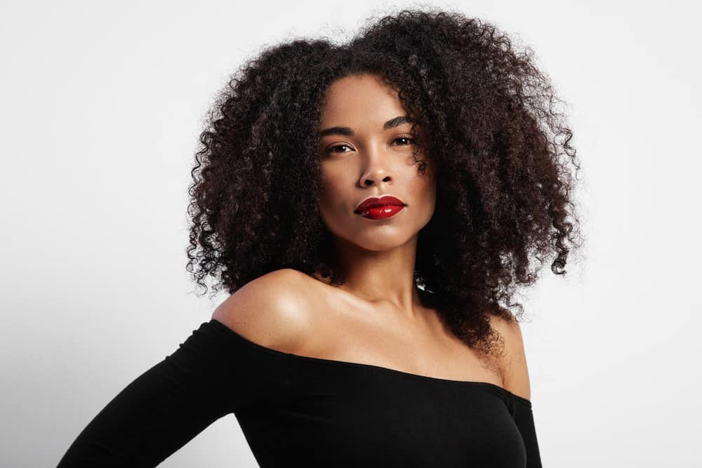 Beautiful back women with curly hair wearing a black dress and red lipstick.