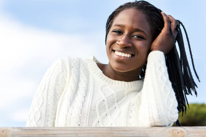 African American female wearing a white sweater with 4C hair.