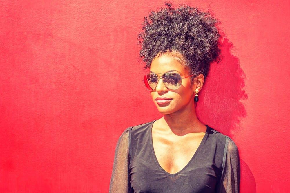Black women wearing black sheer top in sun with black seed oil treated curly hair.
