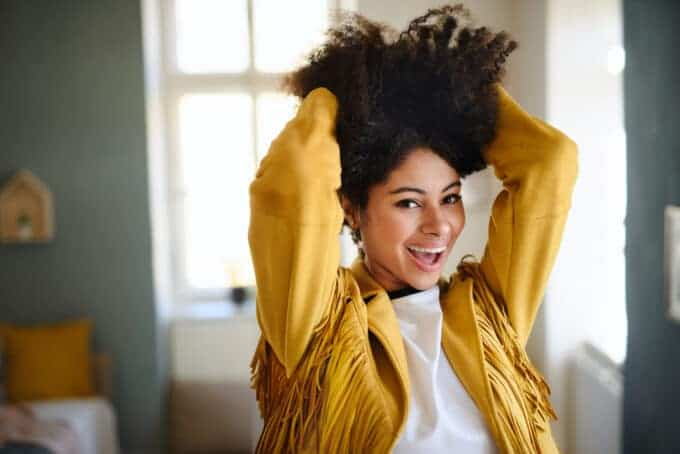 Adult female with a yellow cowgirl jacket rubbing her fingers through her naturally curly hair