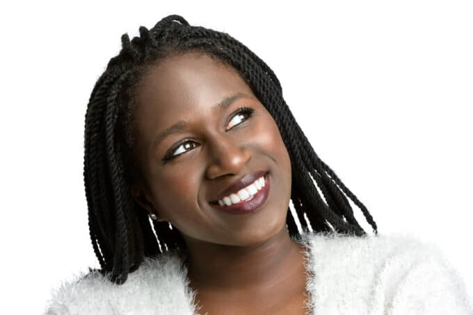 African American woman with braids wearing burgundy lipstick and silver earrings.