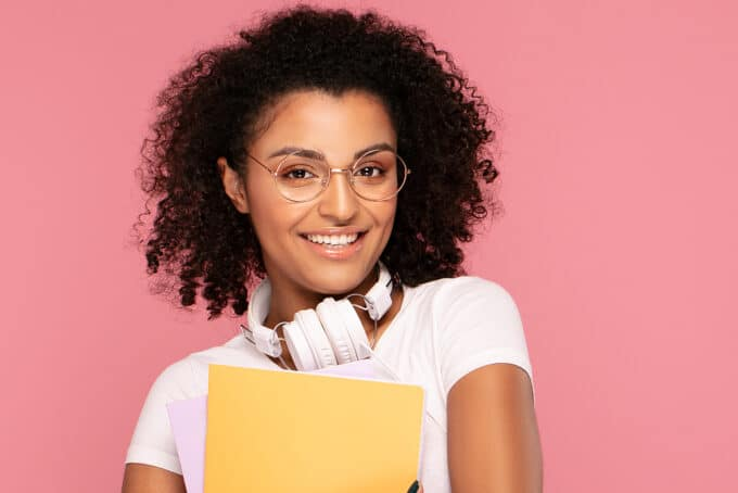 Cute black woman with round eye glasses, pink lipstick, curly, white Dr. Dre headphones, and a yellow notebook.