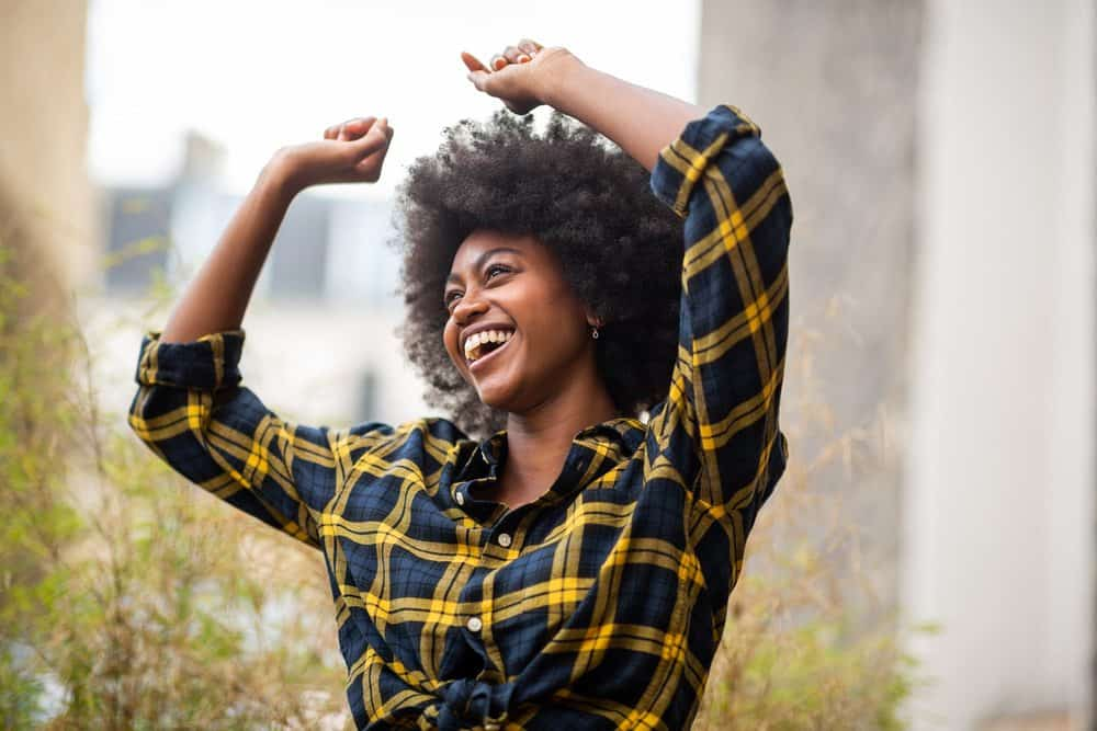 Cheerful woman with her arms raised in the air while dancing outdoors.