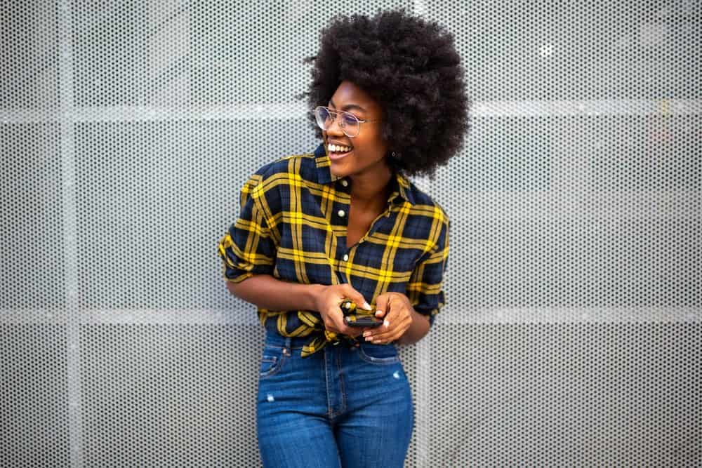 Black girl wearing blue jeans with a blue and yellow shirt and glasses while using a mobile phone.