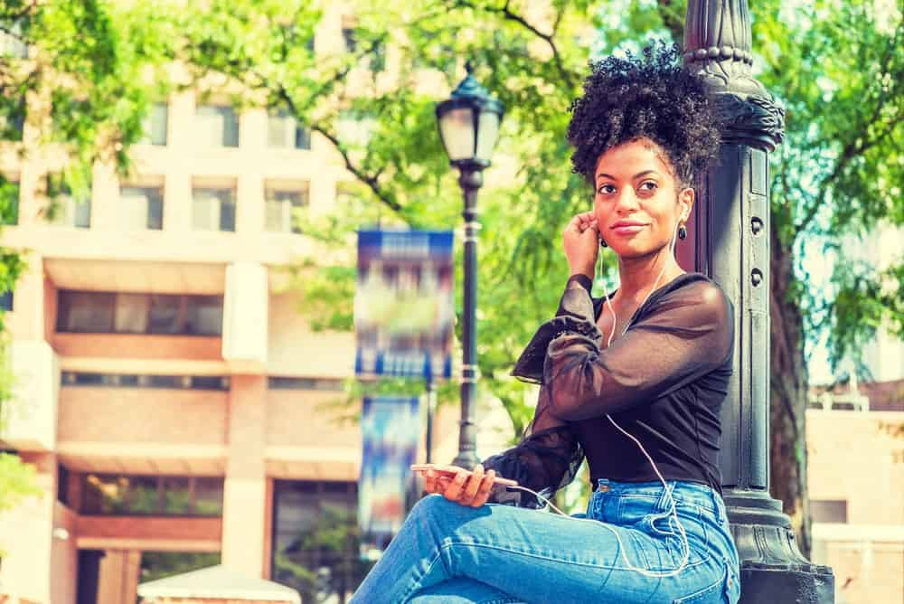 African American female sitting on park bench listen to Pandora music with iPhone headphones.