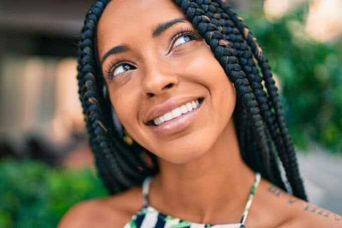 Close-up image of African American female wearing a braided ombre protective style.