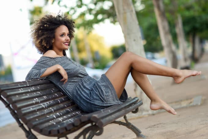 Black women with ombre natural hair sitting on a stained park bench while kicking her legs.