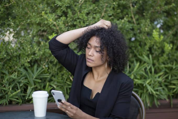 Cute black woman wearing a black dress holding her type 4A curly hair.
