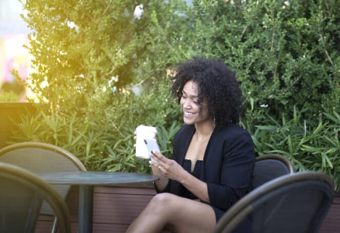 African American adult female wearing a black dress while sitting at an outdoor restaurant.