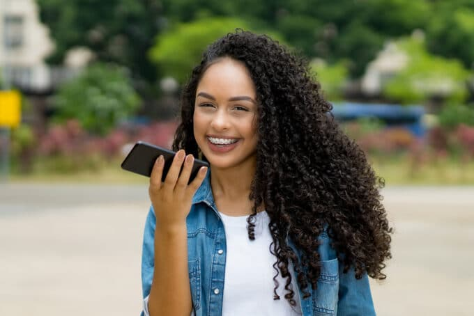 African American woman talking on a mobile phone with t3 curly hair wearing a blue jean shirt.