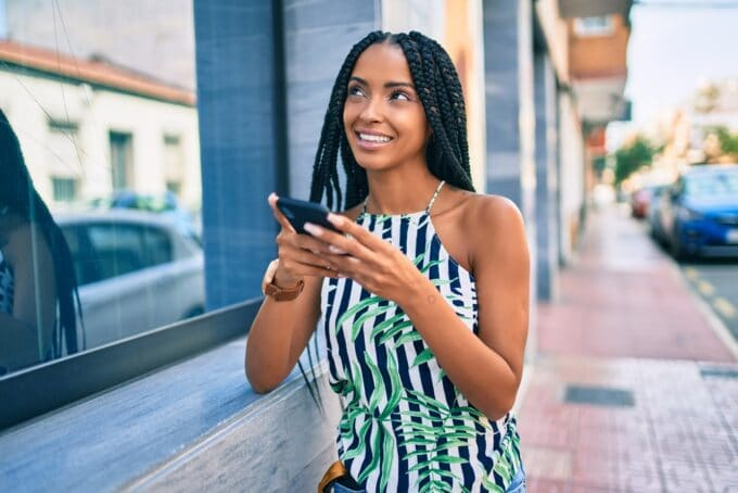 Black woman with Ghana braids wearing a leather watch, flower-based shirt, and blue jeans while using her iPhone 10.