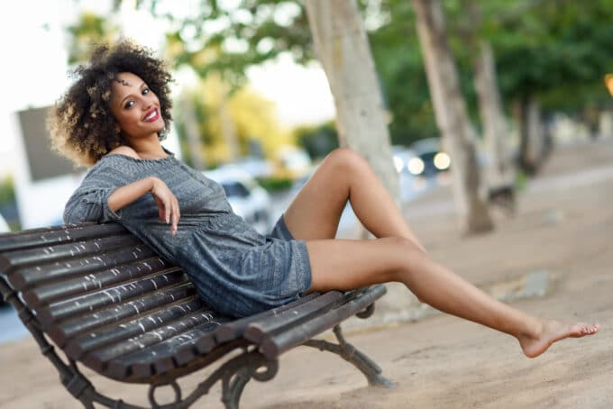 African American female type 4A curly hair sitting on a wooden park bench in New York City wearing a gray dress.