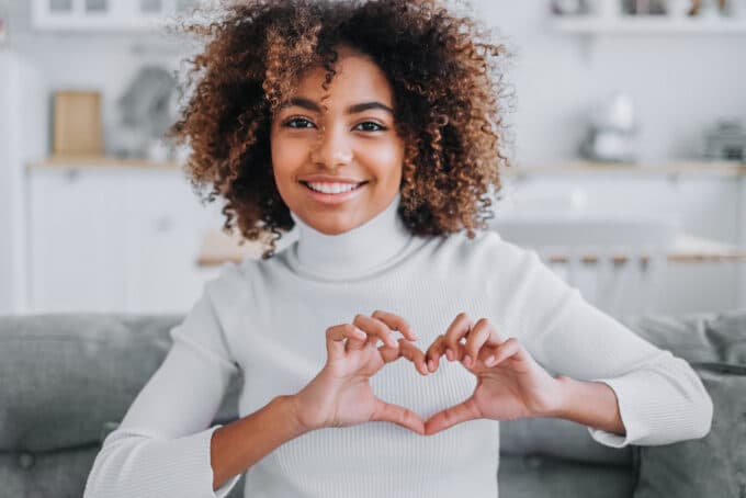 Black female with type 3c curly hair smiling while making a heart symbol with her hands.