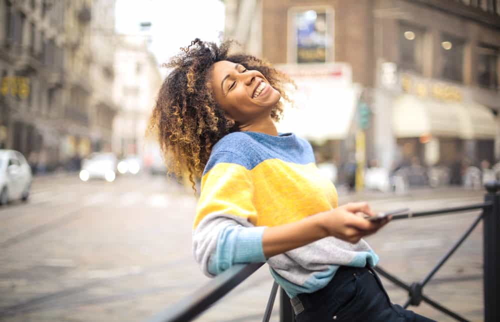 Black women with ombre 4c strands wearing a blue, yellow, and gray sweater with black jeans.