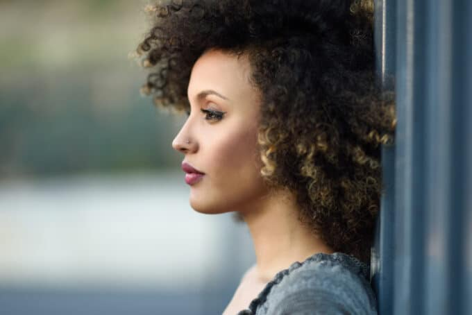 American female with type 4B curly hair, a small nose ring, red lipstick while leaning up against the wall.