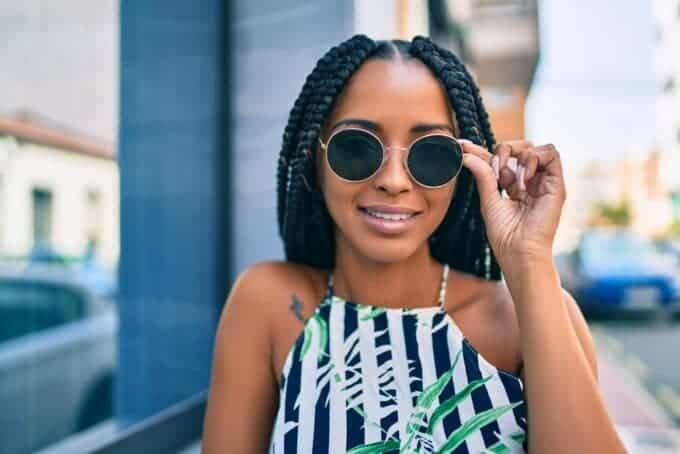 Beautiful black woman wearing crochet braids, sunglasses, pink fingernails, and a blue, green, and white.