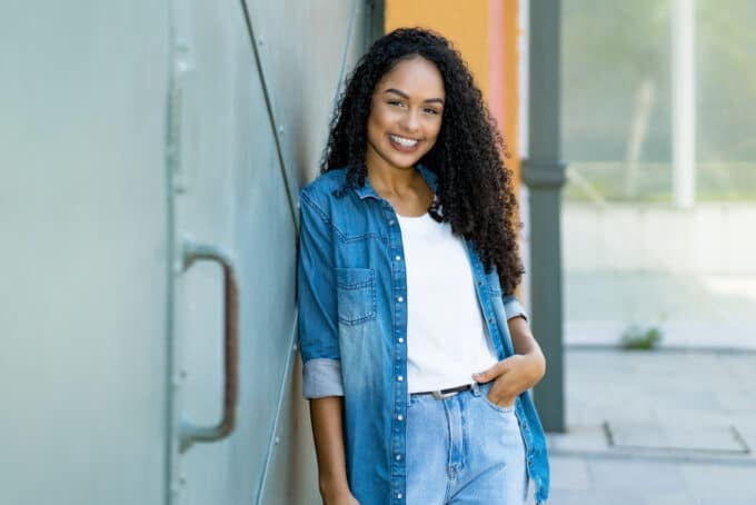 African American women wearing a blue jean outfit and a white t-shirt with type 3c natural hair.