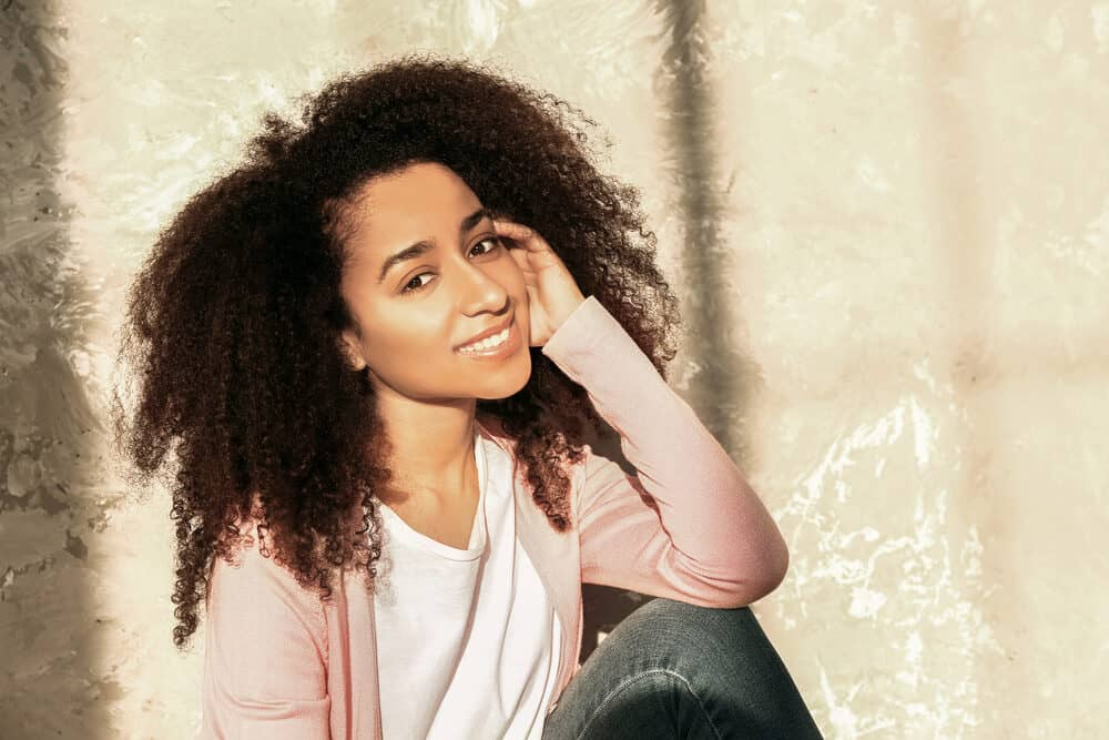 Beautiful African American female sitting on the ground near a grunge wall.