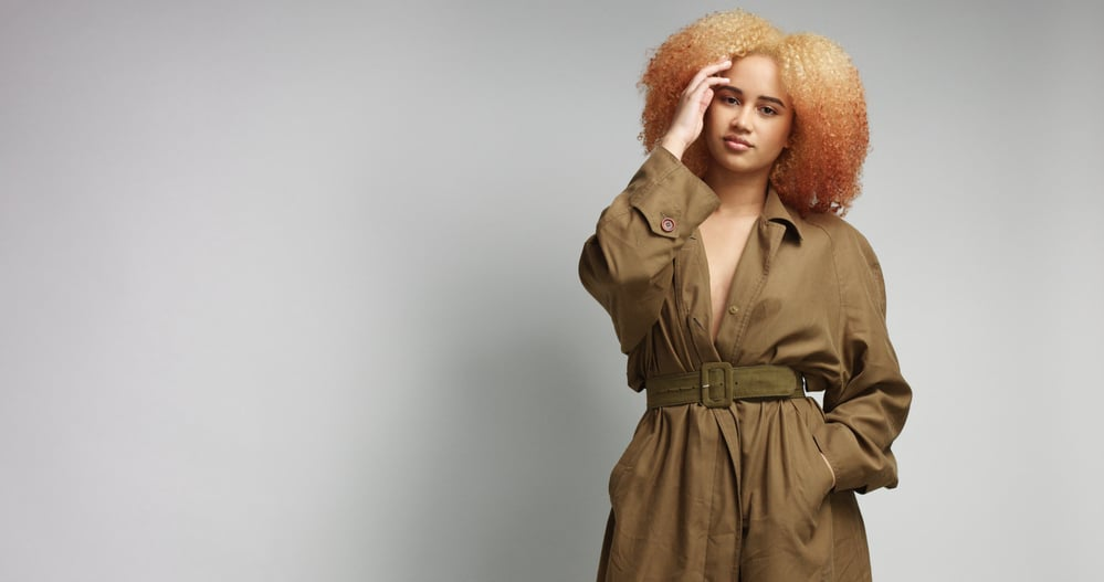 Black women wearing during a photoshoot wearing a khaki coat standing in front of a gray wall