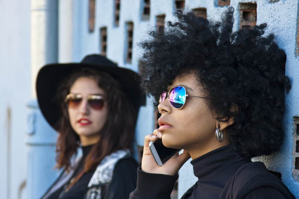 Young women standing beside a friend having a conversation on a mobile phone.