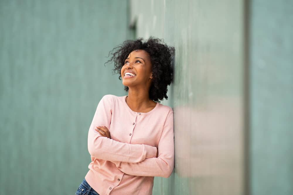 African American female leaning against a green marble wall wearing a pink shirt and casual pants.