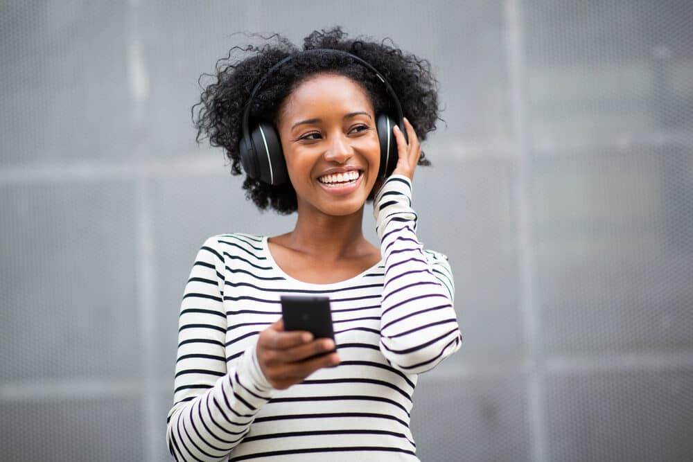 Beautiful black girl listening to wireless Beats Solo headphones paired with her iPhone 12.