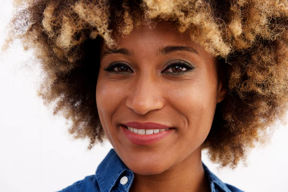 Black women with ombre curly hair wearing a blue collared shirt, eye shadow, and red lipstick.