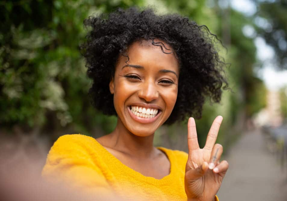 Black female holding up the peace sign with her fingers while taking a selfie with her mobile phone.