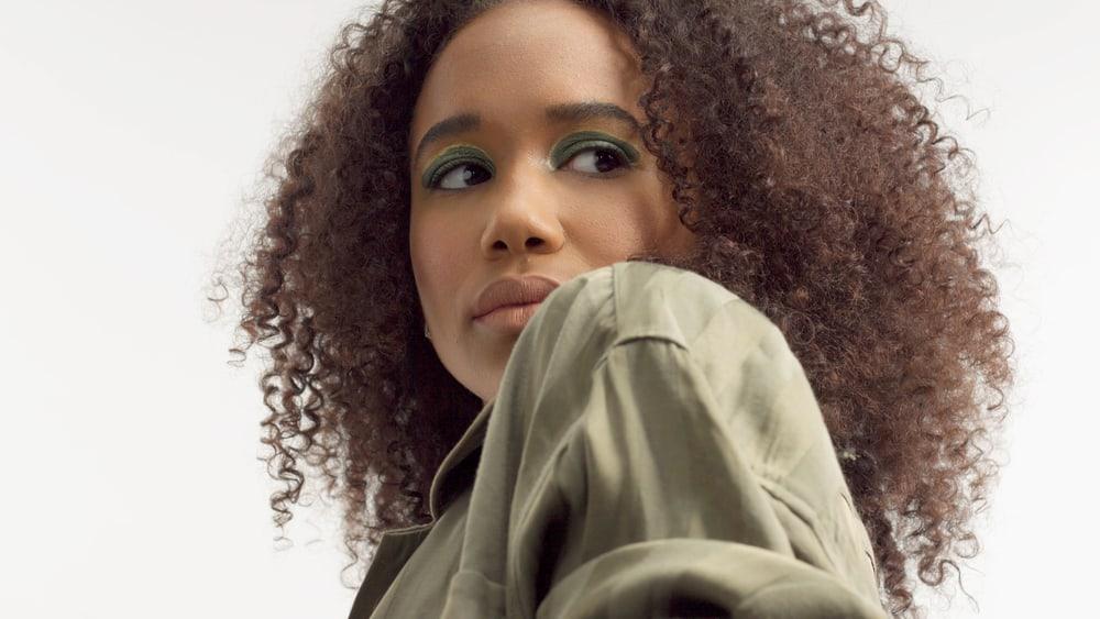 African American female with natural hair wearing metallic green eyeshadow looking back over her shoulder.