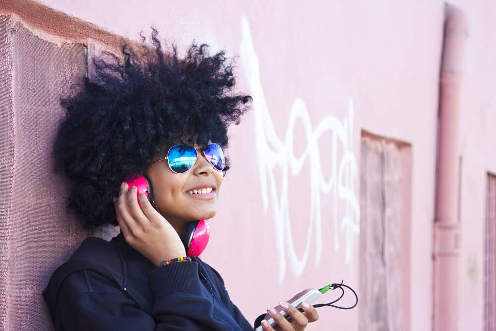 Black girl with natural hair listening to the song Next Day by the Cold Water band on her headphones.