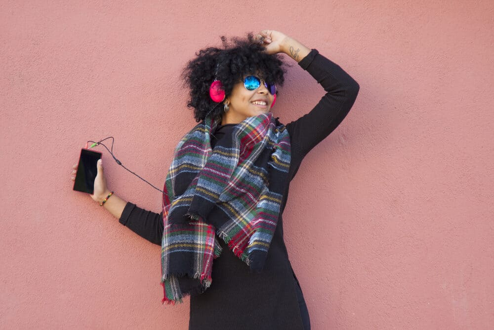 Black women dancing in the street while wearing a black dress, headphones, and a multi-colored winter scarf.