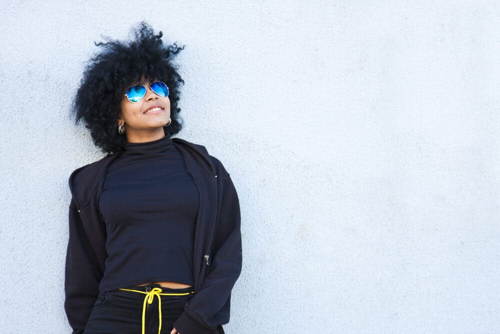 African American women wearing a black jogging suit with a yellow rope belt.