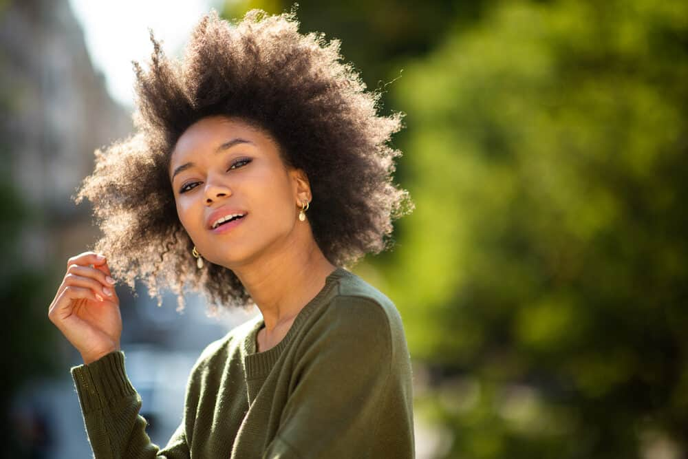 Cute black girl standing outside wearing a green sweater and gold earrings with curly hair.