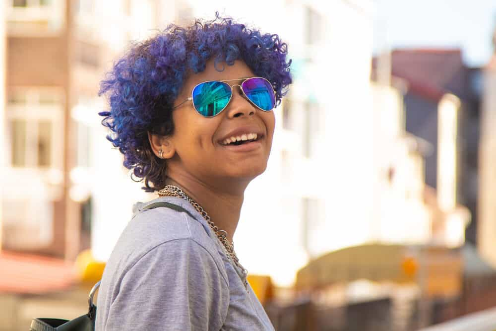 Hispanic female with blue hair looking back over her shoulder and smiling at the camera.