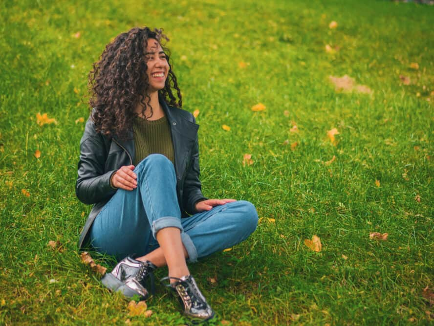 Beautiful brunette woman with very long curly hair sitting outside in the grass with her legs crossed.