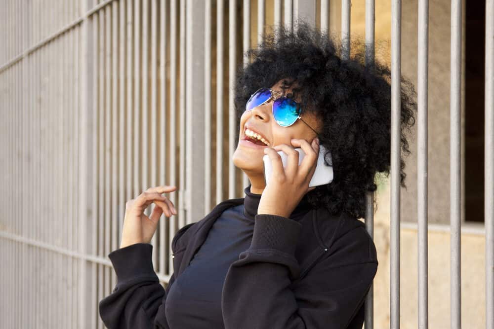 Woman leaning up against a fence, talking on a mobile phone, while laughing at her friend's joke.