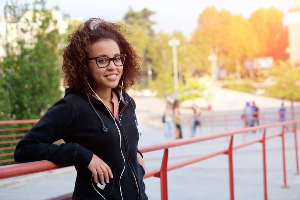 American female wearing eyeglasses while standing outside and listening to music on earphones.