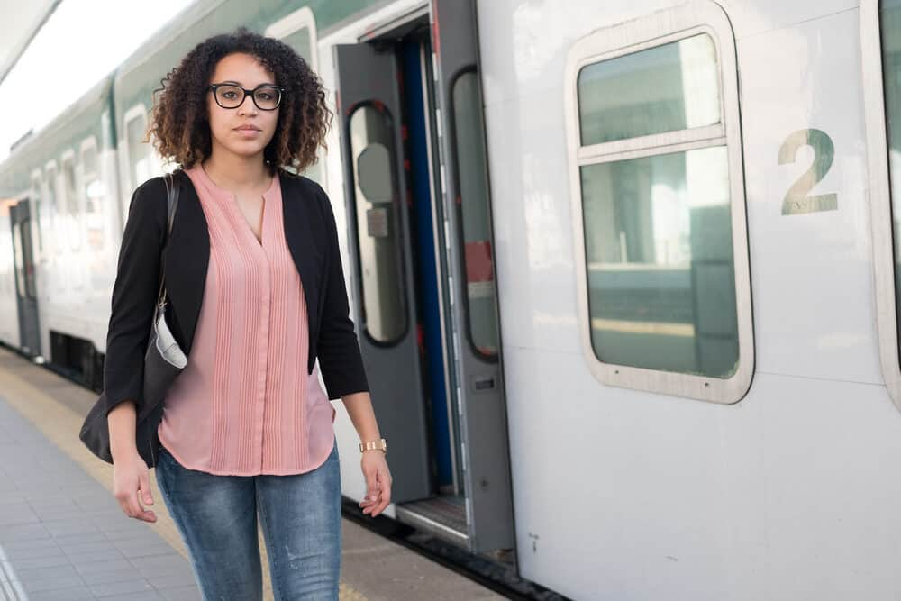 Black girl wearing a pink shirt, black sports coat, black purse, and blue jeans.