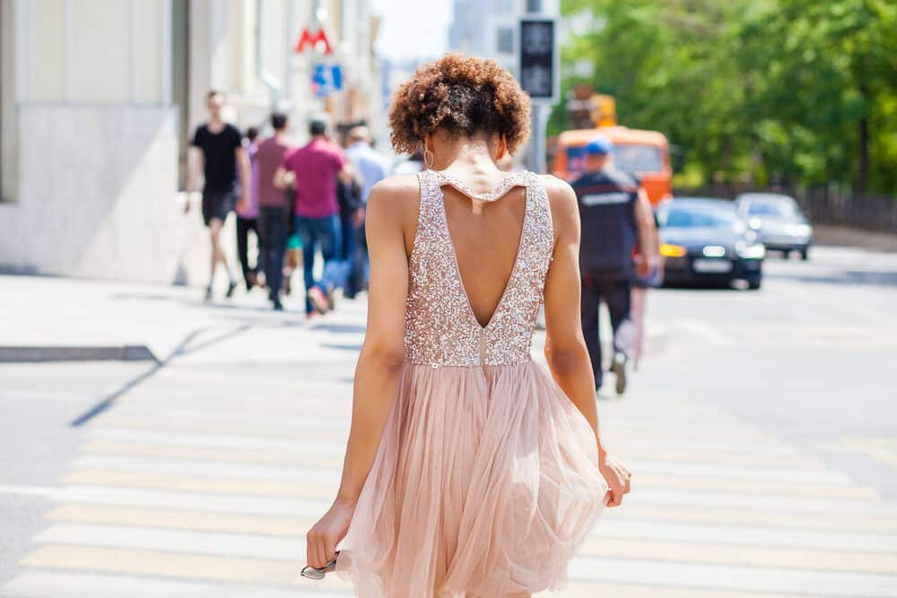 Skinny black girl with type 4 curls wearing a prom-style dress with sequins.