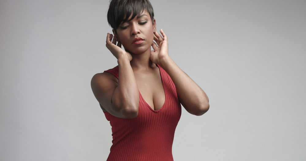 Black girl with relaxed hair after getting a silk press wearing a red dress and red lipstick.