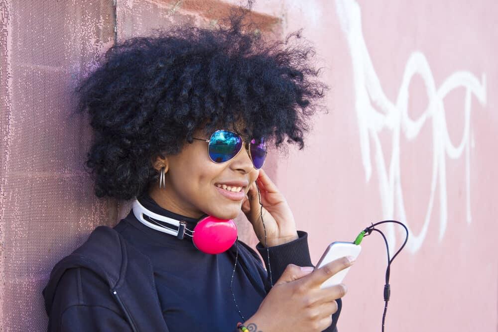 Black women standing outside having a hard time hearing her music on broken earphones.